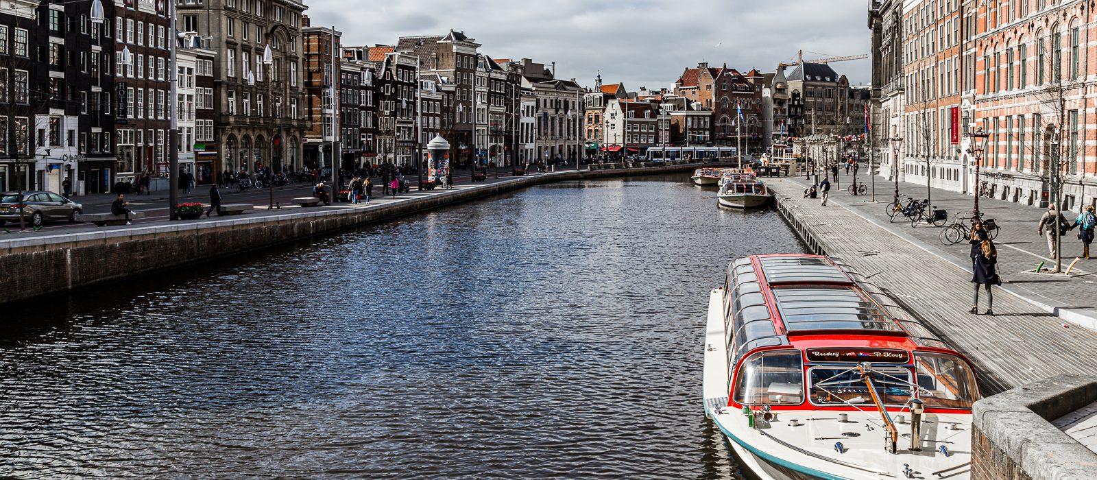 Dieses Foto von Amsterdam zeigt eine Gracht mit Boot und die wunderschönen für Amsterdam typischen Häuser