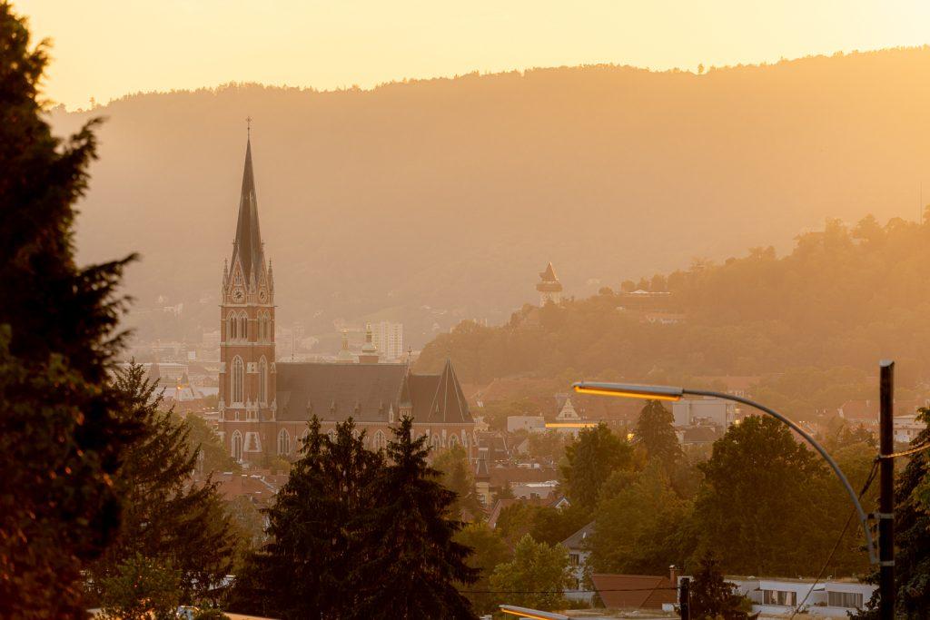 Herz Jesu Kirche und Uhrturm Graz im Sonnenuntergang