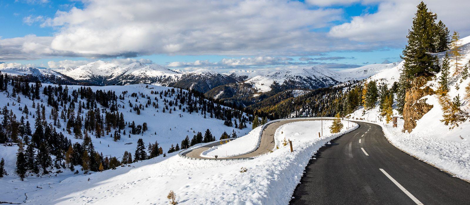 Straße meandert abwärts, im Hintergrund tolle Berge, blauer Himmel und stimmungsvolle Wolken