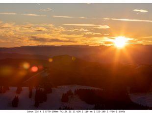 Sonnenuntergang in den Bergen mit etwas Schnee im Vordergrund und passenden Lens Flares