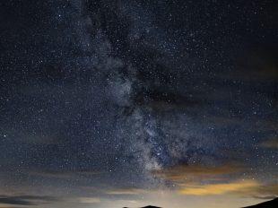 Kleiner See und Berge bei Nacht ganz dunkel im unteren Teil des Bildes. Der Großteil des Bildes zeigt den Sternenhimmel mit vereinzelten orangenen Wolken. Durch die Mitte zieht sich das galaktische Zentrum der Milchstraße.