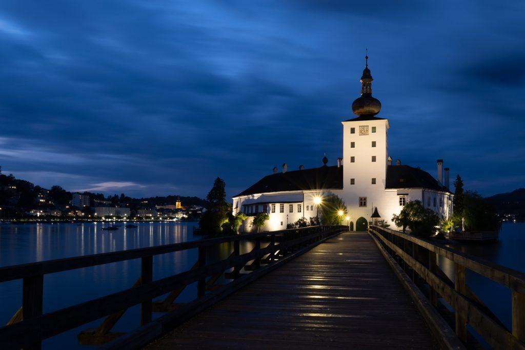 Eine Brücke führt direkt auf das Schloss Ort zu, das sich in der Bildmitte hell erhebt. Die Wolken sind durch die Langzeitbelichtung verschwommen und sind blau bis schwarz durch die blaue Stunde.