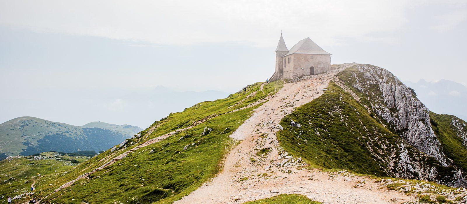 Wir befinden uns auf einem über 2000m hohen Berg. Auf einer Anhöhe steht ein gemauerte Kapelle, hier im Hintergrund zu sehen. Im Vordergrund befindet sich die typisch kurze Wiese und von rechts und links zusammenlaufende Wanderwege. Diese bündeln sich hin zur Kapelle. Ganz hinten sind Silhouetten einiger Berge zu sehen.