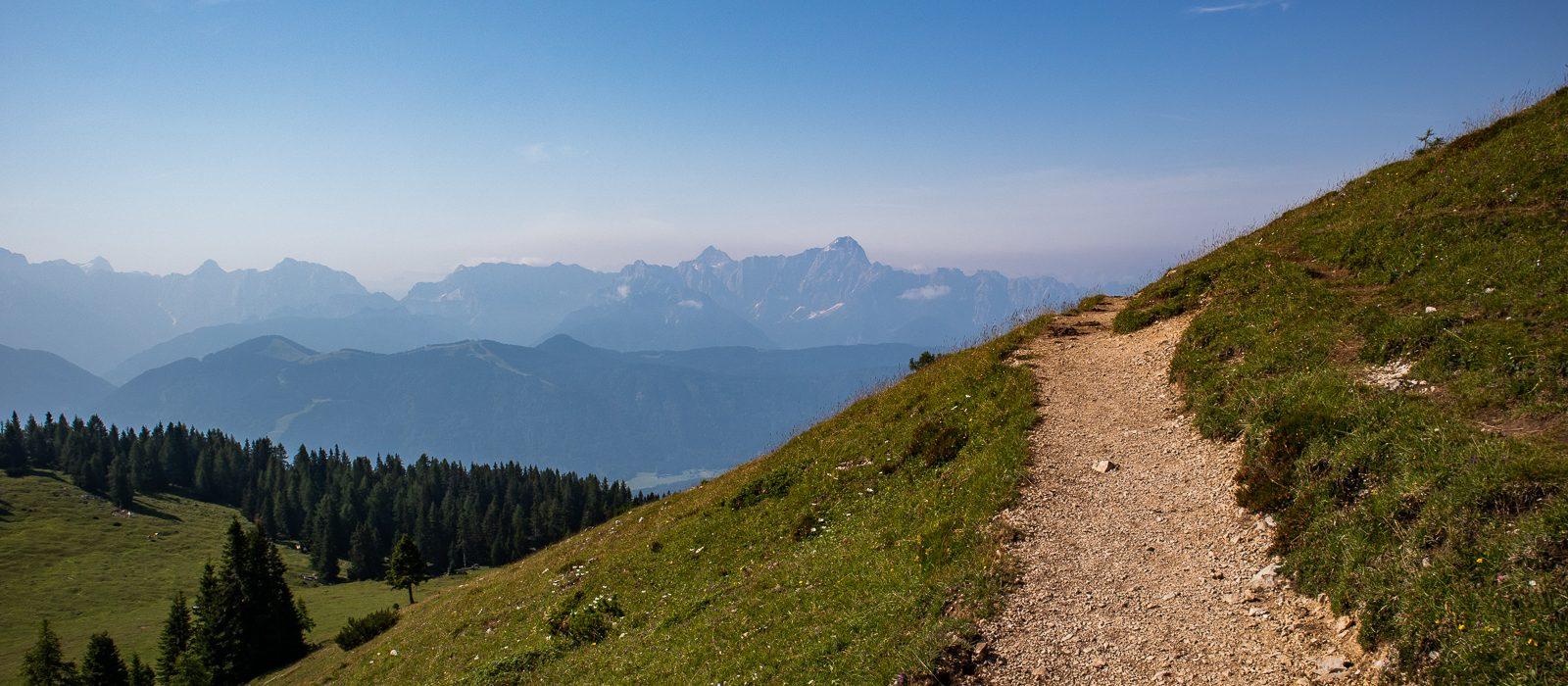 Ausblick auf die Julischen Alpen vom Dobratsch. Wir sehen einen Wanderweg, der ins Bild hinein verläuft, dann aber ins Unsichtbare Verschwindet. Im Hintergrund sieht man das Bergmassiv der Julischen Alpen.
