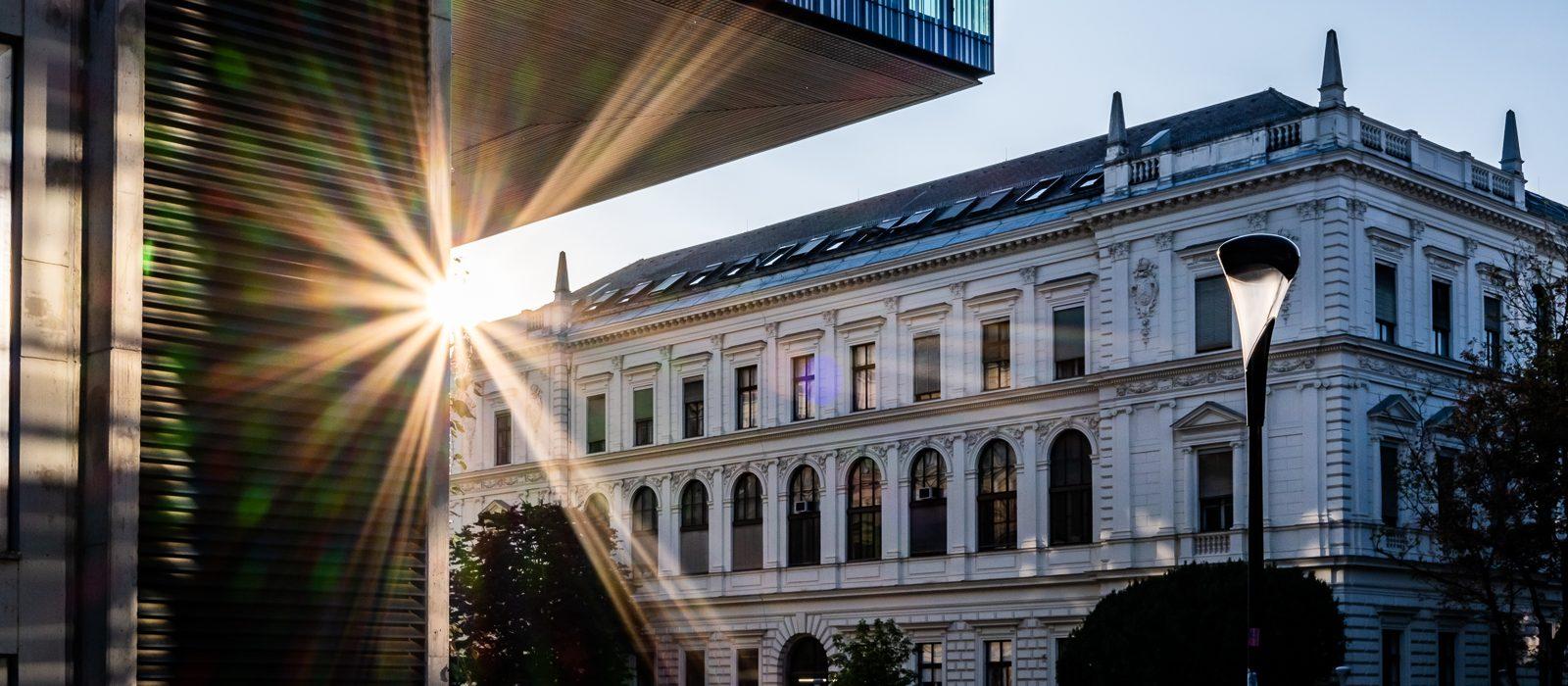 Sonnenuntergang Grazer Universität mit Sonnensternen, altem und neuen Gebäuden