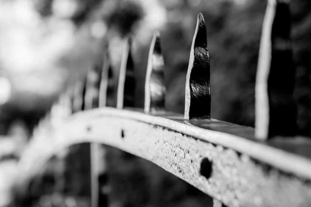 Schwarzweiß Foto, das einen Zaun mit Spitzen zeigt.