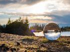 Im Vordergrund ist eine Fotokugel in der sich der Horizont mit einem See und einer Goldenen Stunde Stimmung spiegelt