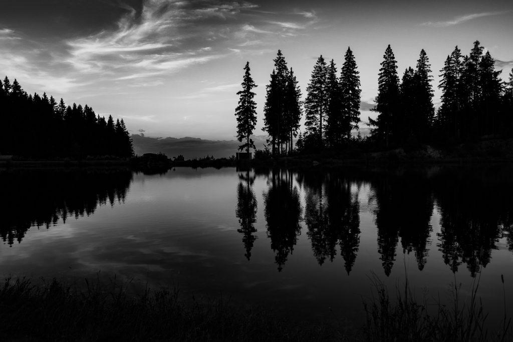 Ein See mit Nadelbäumen am Horizont, die sich im Wasser spiegeln. Dazu sieht man interessante Wolken.