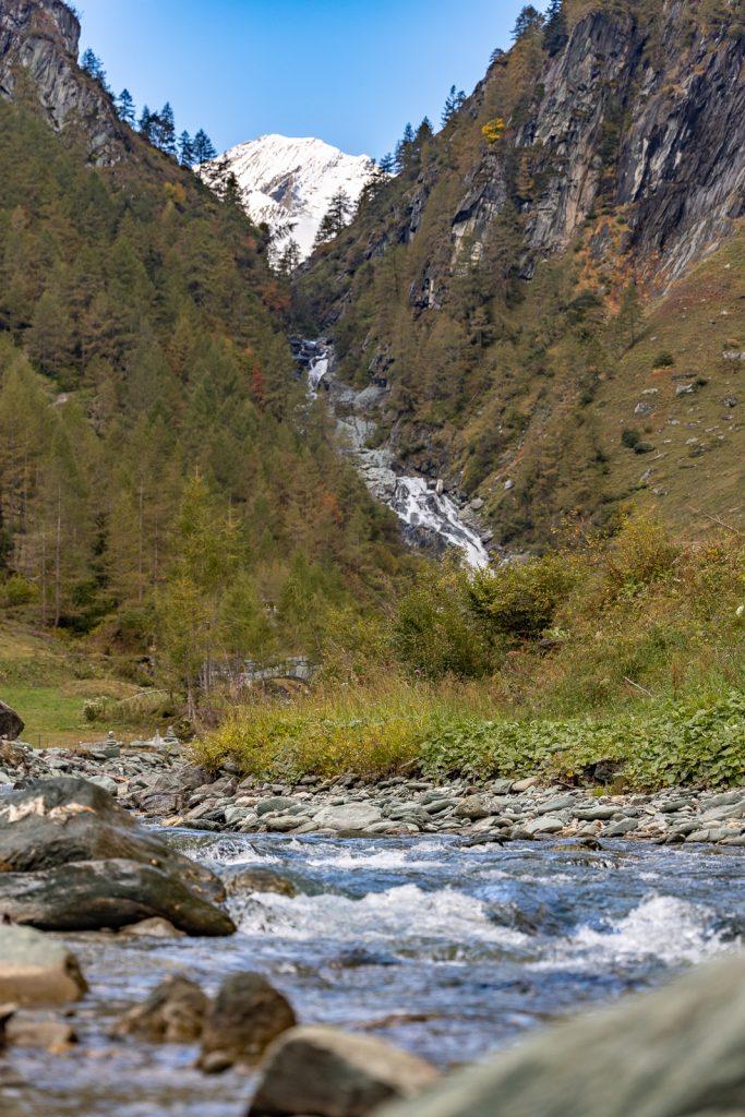 Im Vordergrund ist ein Fluss, dahinter die Umballfälle und ganz hinten oben sieht man die schneebedeckte Rötspitze
